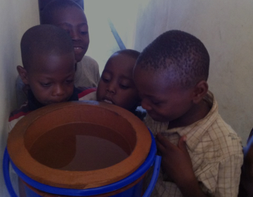 Kids looking at a pot of water